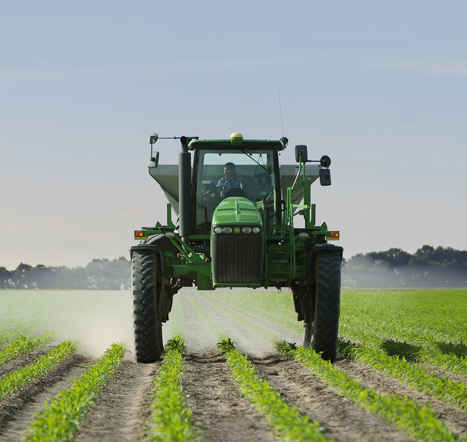 Tractor spreading fertilizer on young corn crop field