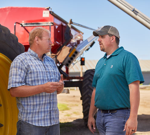 ADM representative talking with farmer next to fertilizer spreader