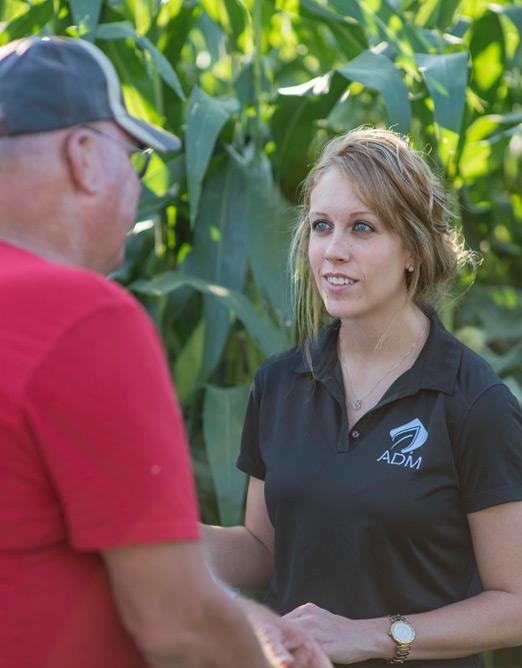 Female ADM representative talking to male farmer in corn field